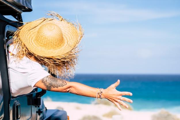 Szczęście i radość dla koncepcji osób podróżujących styl życia ze szczęśliwą młodą kobietą oglądaną z tyłu świętują lato i plażę za oknem samochodu
