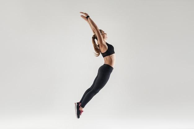 Szczęście i radosna kobieta skacze wysoko i ręce do góry. studio strzał, szare tło