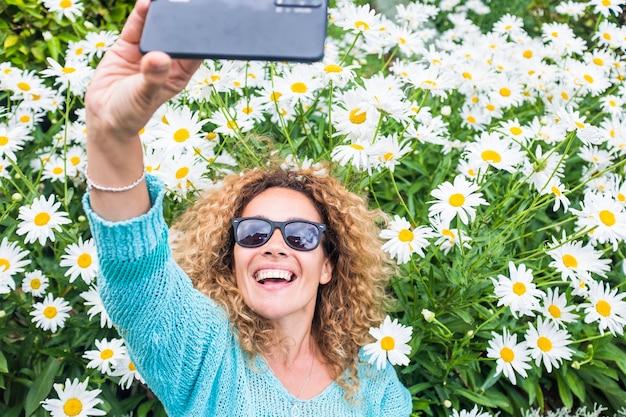 Szczęście i radosni ludzie z piękną dorosłą kobietą otwierającą ramiona i cieszącą się naturalną i kwiatową powierzchnią w parku