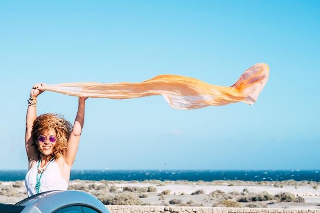 Szczęście i wolność radość koncepcja ludzi z atrakcyjnym podróżnikiem w średnim wieku z kabrioletu uśmiechnięty i cieszący się zabawą z wiatrem na wakacjach z błękitnym morzem i niebem na powierzchni