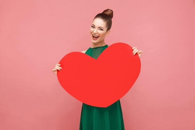 Szczęście kobieta trzyma duże czerwone serce, uśmiechnięty ząb. koncepcja ekspresji emocji i uczuć. studio strzał, na białym tle na różowym tle
