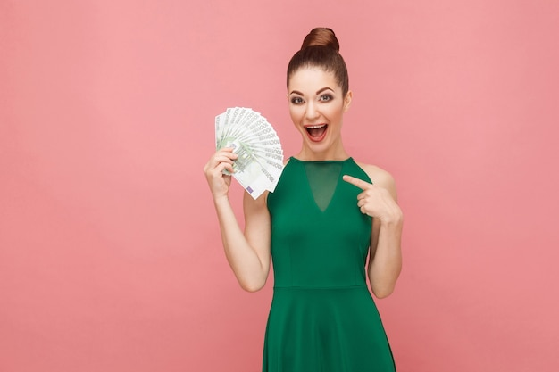 Szczęście kobieta trzyma wiele euro i palcem wskazującym. koncepcja ekspresji emocji i uczuć. strzał studio, na białym tle na różowym tle