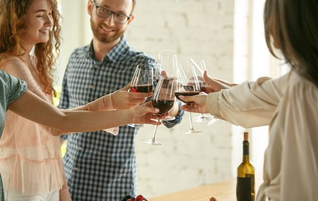 Szczęście. ludzie brzęczą kieliszkami z winem lub szampanem.