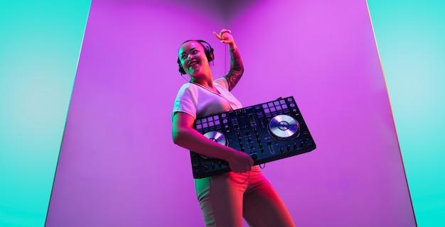 Szczęście. młoda kobieta muzyk w słuchawkach wykonujących na fioletowym tle w świetle neonowym. pojęcie muzyki, hobby, festiwalu, rozrywki, emocji. radosny gospodarz imprezy, dj, portret artysty.