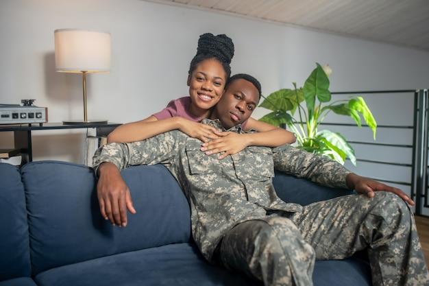Szczęście. młoda piękna afroamerykańska żona przytulająca się przez ramiona wojskowego męża w mundurze szczęśliwego powrotu do domu