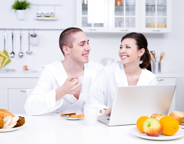 Szczęście młodej pary miłości siedzi w kuchni z laptopem