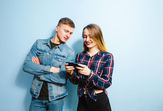 Szczęście na twarzy dwóch przyjaciół, na niebieskim tle, patrząc na telefon.