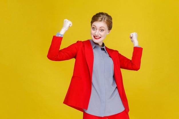 Szczęście optymistyczna czerwona głowa biznesowa kobieta w czerwonym garniturze wygraj
