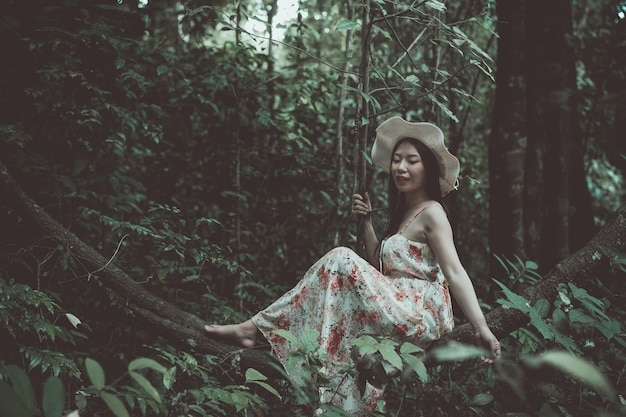 Szczęście piękna azjatykcia kobieta jest ubranym słomianego kapelusz w parku