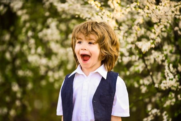 Szczęście. podekscytowany dzieciak. śliczny chłopiec wiosna ogród. międzynarodowy dzień dziecka. szczęśliwe dzieciństwo. zdrowe dziecko. opieka nad dzieckiem. świętuj letnie wakacje. chłopiec natura tło. rozwój dziecka.