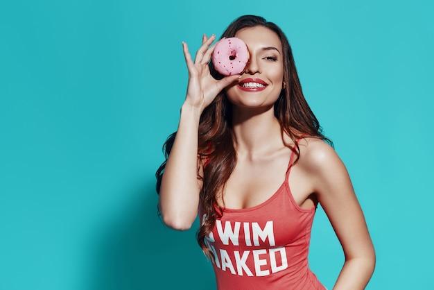 Szczęście podkreśla jej urodę. piękna młoda kobieta w stroju kąpielowym, uśmiechając się i patrząc przez pączka, stojąc na niebieskim tle