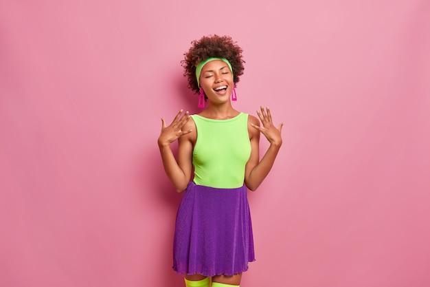 Szczęście, przyjemne chwile życia. rozradowana, zadowolona kobieta o naturalnych kręconych włosach, zamyka oczy, pozytywnie się śmieje, podnosi ręce, ubrana w modny, jasny strój, bawi się