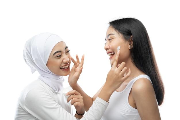 Szczęście śmiejącej się przyjaciółki podczas nakładania kremu do twarzy palcami dłoni