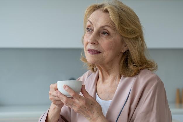 Szczęście starszej kobiety w szlafroku pijącej kawę o poranku śniącej