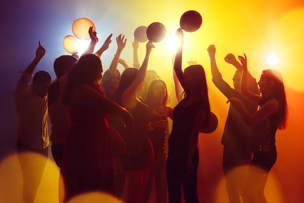 Szczęście. tłum ludzi w sylwetce podnosi ręce na parkiecie na neonowym tle. życie nocne, klub, muzyka, taniec, ruch, młodzież. żółto-niebieskie kolory i poruszające dziewczyny i chłopcy.