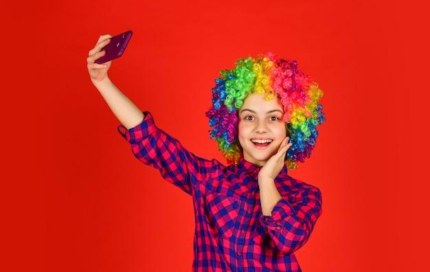 Szczęście z dzieciństwa. dzieciak wygląda śmiesznie we włosach tęczowej peruki. farbowanie włosów u fryzjera. dziecko zabawy. z okazji urodzin. mała dziewczynka kolorowa peruka zrobić selfie na telefon. pozytywny i wesoły.