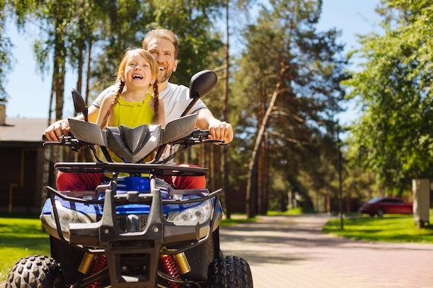 Szczęście. zachwycona urocza dziewczyna uśmiechnięta i prowadząca atv ze swoim tatą