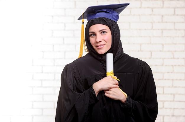 Szczęśliwa absolwentka muzułmańskiej studentki pozuje z dyplomem w pomieszczeniu