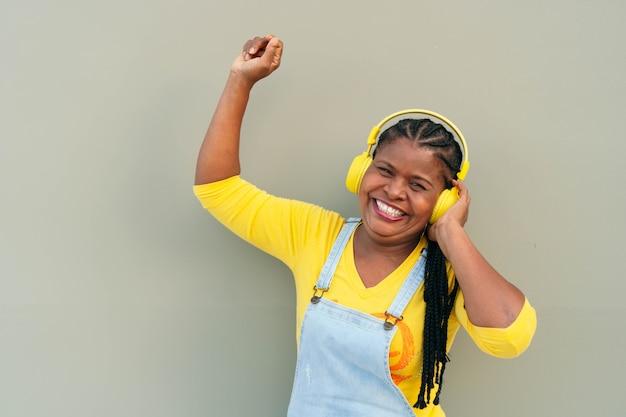Szczęśliwa african american kobieta za pomocą smartfona i ciesząc się muzyką ze słuchawkami na ulicy.