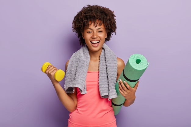 Szczęśliwa afro amerykanka podnosi małe ciężary, trzyma zielony karemat, gotowa do ćwiczeń jogi