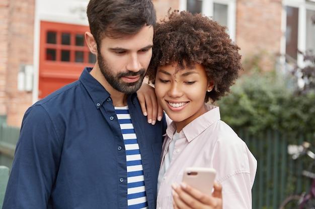 Szczęśliwa afro amerykanka pokazuje na telefonie komórkowym wideo online z sieci społecznościowych brodatemu chłopakowi