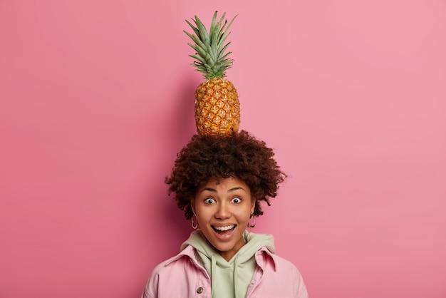 Szczęśliwa afro amerykanka trzyma na głowie pysznego świeżego dojrzałego ananasa, radośnie patrzy w kamerę, bawi się sam na sam z owocami tropikalnymi, ma dobry nastrój