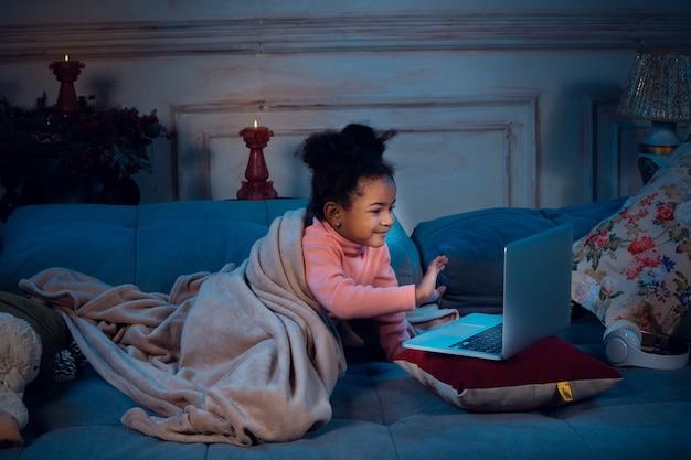 Szczęśliwa afro-amerykańska dziewczynka podczas wideorozmowy z laptopem i urządzeniami domowymi, wygląda na zachwyconą i szczęśliwą. rozmawiać z mikołajem przed sylwestrem, z rodziną, oglądać bajki, pisać tekst.