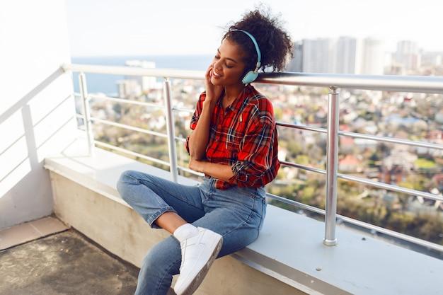 Szczęśliwa afro amerykańska kobieta słuchająca uroczej muzyki przez słuchawki, ubrana w kraciastą koszulę, stojąca na dachu. tło krajobrazu miejskiego.