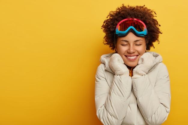 Szczęśliwa afro kobieta nosi maskę narciarską, ciepłe dzianinowe rękawiczki i płaszcz, lubi spędzać czas na świeżym powietrzu. cieszę się, że kobieta w odzieży snowboardowej