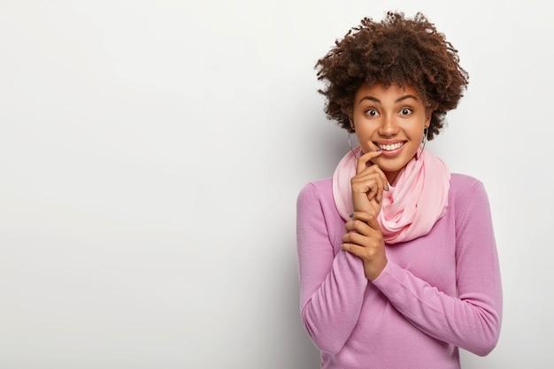 Szczęśliwa afro kobieta z kręconymi fryzurami, dotyka palcem wskazującym ust, ma zębaty uśmiech, ubrana swobodnie