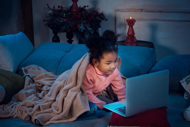 Szczęśliwa afroamerykańska dziewczynka podczas rozmowy wideo z laptopem i urządzeniami domowymi