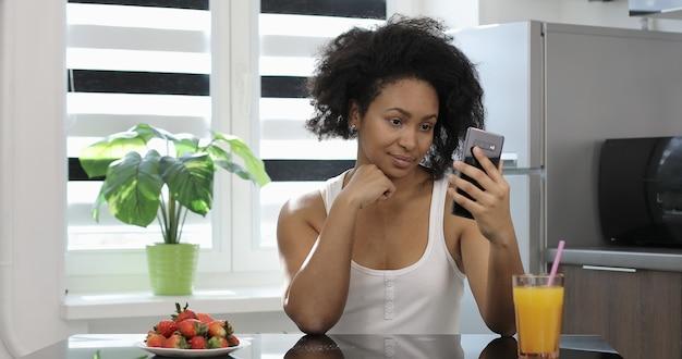 Szczęśliwa afroamerykańska kobieta biznesu komunikująca się przez wideo-cal uśmiechnięta dziewczyna korzystająca z telefonu komórkowego