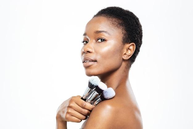 Szczęśliwa afroamerykańska kobieta trzyma pędzle do makijażu na białym tle