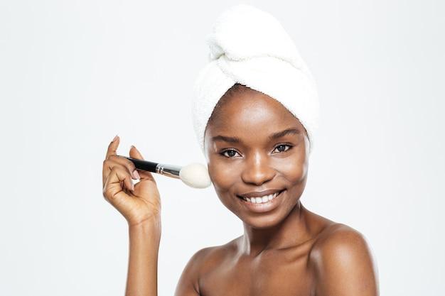 Szczęśliwa afroamerykańska kobieta z pędzlem do makijażu i ręcznikiem na białym tle