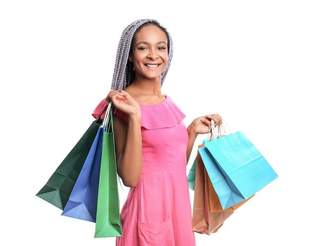 Szczęśliwa afroamerykańska kobieta z torbami na zakupy na białym