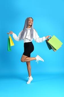 Szczęśliwa afroamerykańska kobieta z torbami na zakupy na niebiesko
