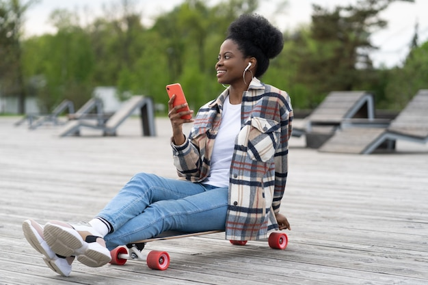 Szczęśliwa afrykańska dziewczyna trzyma smartfona siedzieć w parku miejskim na longboard zrelaksowany słuchać muzyki i wiadomości