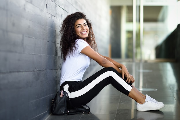 Szczęśliwa afrykańska kobieta siedzi na miastowej podłoga z czarną kędzierzawą fryzurą.