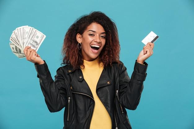Szczęśliwa afrykańska kobieta trzyma pieniądze w skórzanej kurtce