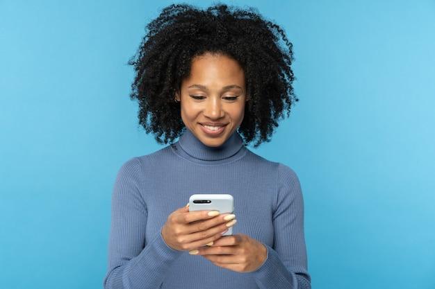 Szczęśliwa afrykańska kobieta tysiąclecia z kręconymi włosami na czacie w mediach społecznościowych, przy użyciu telefonu komórkowego na białym tle