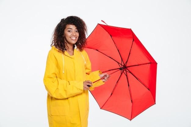 Szczęśliwa afrykańska kobieta w płaszczu pozuje z parasolem