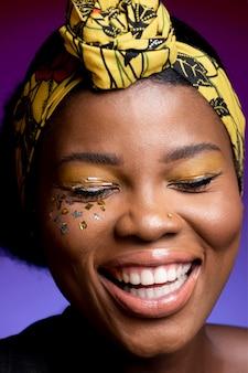 Szczęśliwa afrykańska kobieta w skórzanej kamizelce z błyszczącymi konfetti na policzkach
