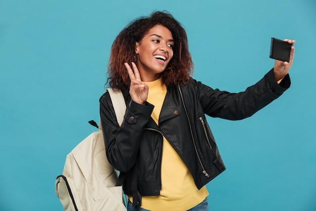 Szczęśliwa afrykańska kobieta w skórzanej kurtce z plecakiem robi selfie