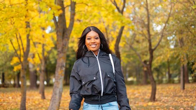 Szczęśliwa afrykańska kobieta z uśmiechem w modnych codziennych ubraniach z modną kurtką chodzącą w naturze z kolorowymi żółtymi jesiennymi liśćmi