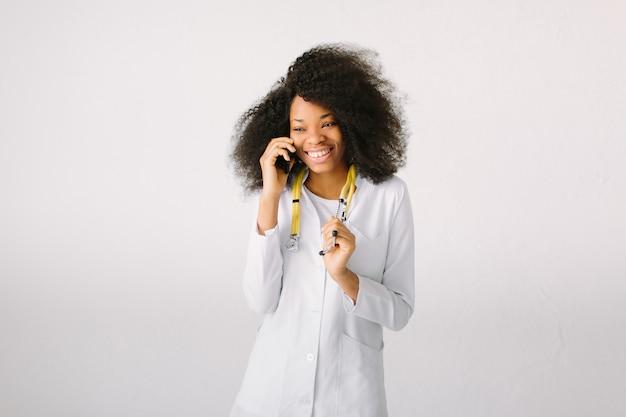Szczęśliwa afrykańska medyczna stażysta lekarka na studiu z stetoskopem w szpitalu na białym tle i opowiadać przez telefon