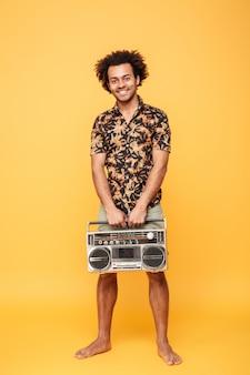 Szczęśliwa afrykańska mężczyzna pozycja z magnetofonem