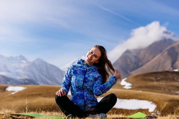 Szczęśliwa aktywna młoda dziewczyna w niebieskiej kurtce podróżuje przez kaukaskie góry, uśmiechając się