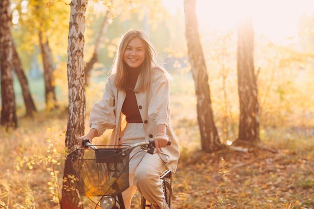 Szczęśliwa aktywna młoda kobieta jazda na rowerze vintage w parku jesień o zachodzie słońca