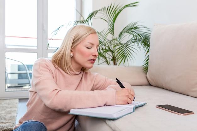 Szczęśliwa albinoska kobieta siedząca na wykładzinie podłogowej podczas studiowania lekcji korzystanie z książki z notatkami.