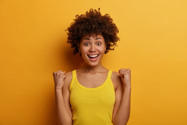 Szczęśliwa, ambitna ciemnoskóra dziewczyna robi pompkę pięścią, świętuje dobre wieści i osiągnięcie celu, cieszy się z doskonałego wydarzenia, nosi zwykłą żółtą koszulę, pozuje w pomieszczeniu, śmieje się pozytywnie, czuje triumf